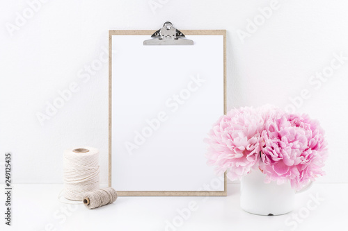 clipboard mock up with blank sheet of paper (DIN A4, portrait format), two yarn spools and a bunch of pink peonies on a white table - copyspace for design or text