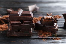 Pieces Of Black Chocolate On Wooden Table
