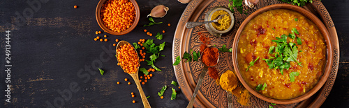 Indian dal. Food. Traditional Indian soup lentils. Indian Dhal spicy curry in bowl, spices, herbs, rustic black wooden background. Top view. Authentic Indian dish. Banner. Flat lay
