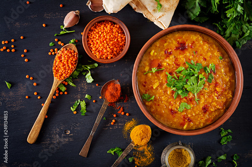 Obraz Indian dal. Food. Traditional Indian soup lentils.  Indian Dhal spicy curry in bowl, spices, herbs, rustic black wooden background. Top view. Authentic Indian dish. Overhead. Flat lay - fototapety do salonu