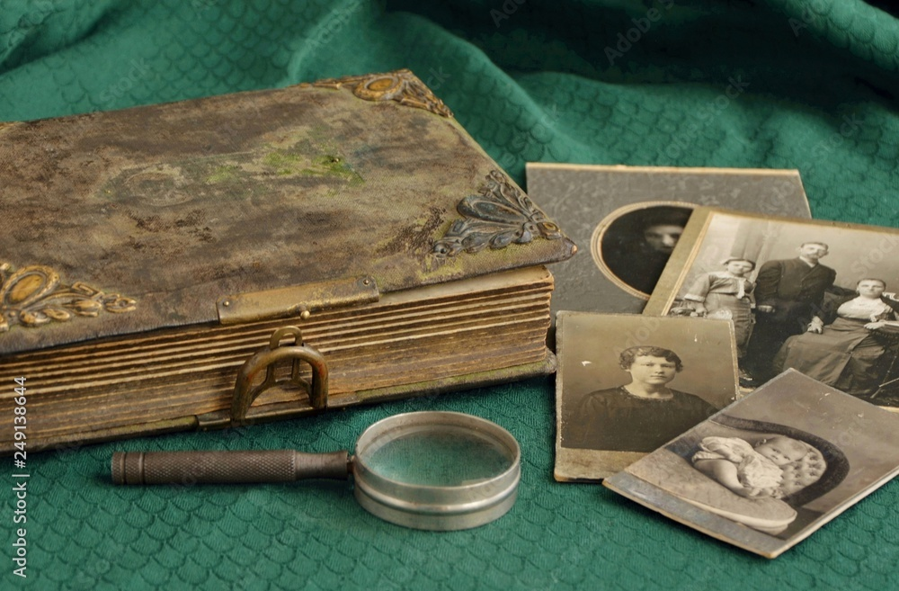 Fototapeta Old photo album and historical photos of family on a green tablecloth.