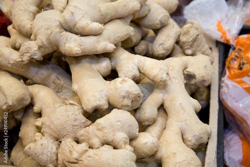 Fototapeta Fresh ginger on the market. Close-up. Oriental spices. Ginger in the vegetable street market. Ginger in the supermarket. Ginger background. Street vegetable market. obraz
