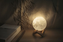 Moon Lamp On Desk, Light At Night, Reading Book On Wooden Table, With Chinese Blinds And Wooden Pencil And Moonlight