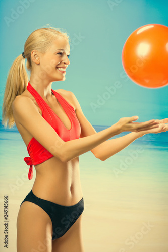 Fotografia  Young beautiful happy smiling blond woman in sportswear playing with red gym bal
