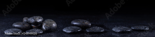 Poster Zen Panoramic image of zen stones with water drops on a black background