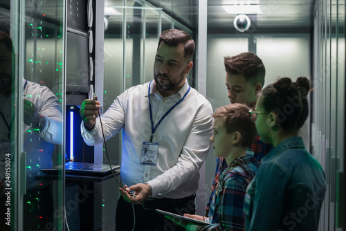 Photo  IT technician showing cable to children