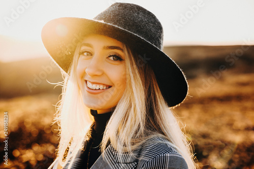 Fotografía  Portrait of a beautiful caucasian blonde female wearing hat laughing against beautiful sunrise while exploring new places while traveling around the world