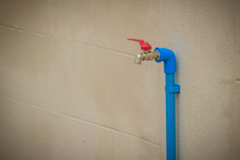 Grungy Bronze Field Faucet Connected With Blue PVC Pipe In White Wall Background.