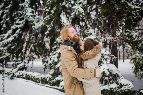 Fotografia  Young Caucasian boy with a beard and a girl have a date outdoors in the winter p