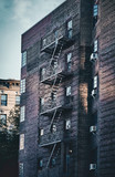 Old building with fire escape at sunset, color toned picture, New York City, USA. - 249160462