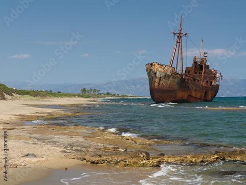 In de dag Schip Rusty big ship shipwreck on Selinitsa beach under a deep blue sky at Gytheio Greece.