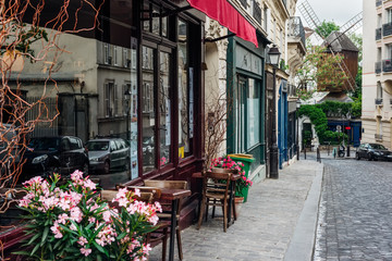 Fototapeta Paryż Cozy street with tables of cafe and old mill in quarter Montmartre in Paris, France