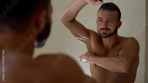 Macho man applying antiperspirant to armpit, preparing to workout in gym Canvas Print