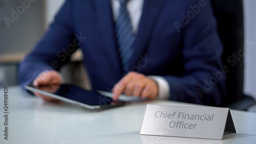 Male chief financial officer planning company budget on tablet pc, office work Canvas Print