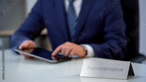 Diplomatic representative working using tablet pc, sliding and reading files Wallpaper Mural