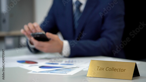 Fototapeta Tax collector using smartphone at work, checking debt statistics in diagrams
