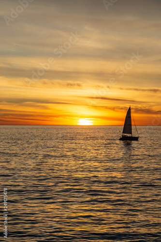 Tuinposter Pier A silhouetted sailing boat on the ocean, against a sunset sky