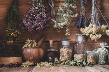 Dried Herbs Hanging Over Bottl...