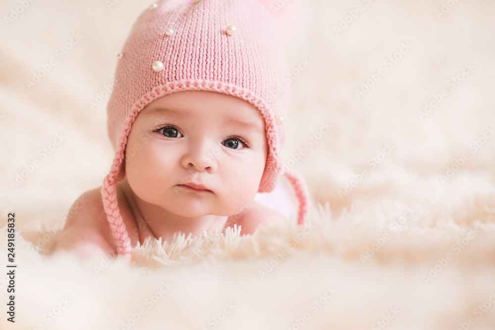 Fototapety, obrazy: Cute baby girl wearing knitted hat lying in bed closeup. Looking at camera. Childhood.