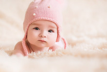 Cute Baby Girl Wearing Knitted Hat Lying In Bed Closeup. Looking At Camera. Childhood.