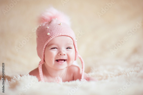Happy baby girl wearing stylish knitted hat lying in bed close up. Childhood.