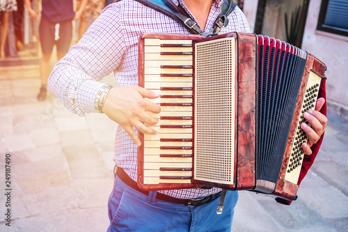 Photo artist musician playing a melody on the accordion on a city street