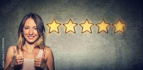 Obraz Сheerful beautiful woman smiling showing thumb up like gesture choosing five stars rating. - fototapety do salonu