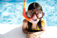 Portrait Of Little Girl Wearing Snorkel And Oversized Diving Goggles Leaning On Poolside