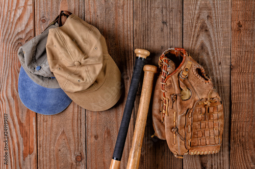 Photo  Baseball Glove and Hats hannging from a nail in a wood wall