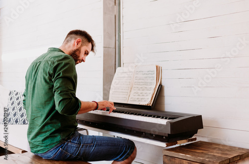 Young man playing electric piano at home studio - 249200297