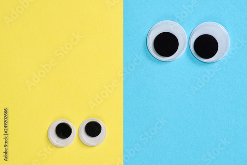 Two pair googly eyes on blue-yellow background look at each other. Mad funny toys eyes close up.