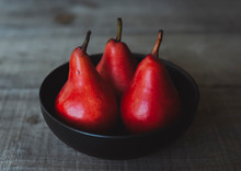 Close-up Of Fresh Red Pears In Bowl On Wooden Table