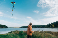 Side View Of Man Flying Kite W...