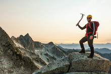 Portrait Of Male Hiker Holding Grappling Hook While Standing On Mountain Against Clear Sky During Sunset