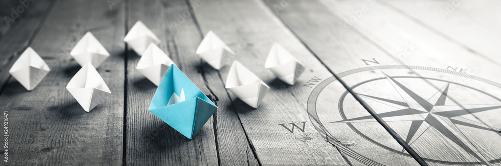 Fototapeta Blue Paper Boat Leading A Fleet Of Small White Boats With Compass Icon On Wooden Table With Vintage Effect - Leadership Concept