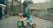 Little toddler riding trike in grandparents backyard