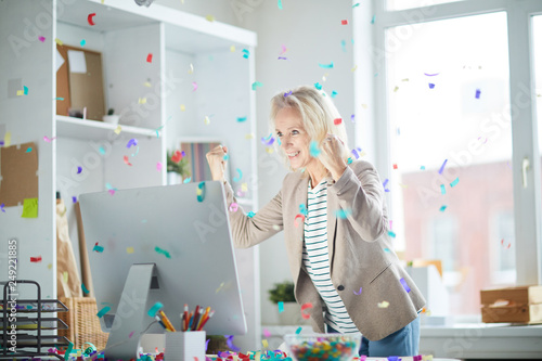 Photo Portrait of excited mature woman celebrating success in office and looking at co