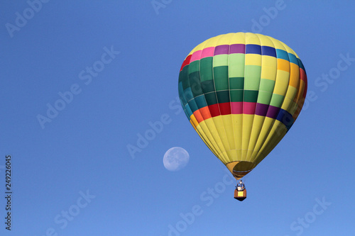 Fotografia, Obraz  Hot air balloon in flight with moon in the background