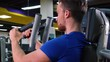 A young fit man trains on a machine in a gym - closeup