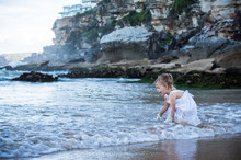 Little Girl Playing With Water In A Beautiful Beach With Rocks In Australia