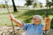 Leinwandbild Motiv Cheerful senior woman on a swing at a playground