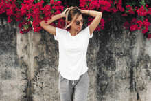 Woman In White T-shirt On Grey Background With Spring Flowers