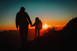 father and little daughter travel in mountains at sunset