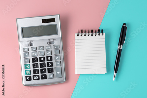 Fotografiet Calculator and notepad on pastel pink and blue background