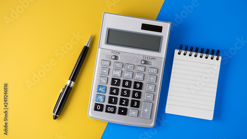 Calculator on vivid yellow and blue background Fototapet