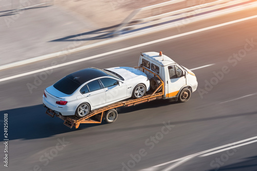 Photo  Recovery truck to transport a car on the highway in the city