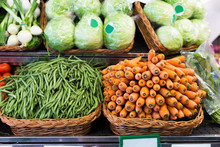 Green Beans And Carrots In Wicker Baskets On Counter Of Vegetable Store