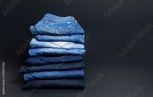 Fotografie, Obraz  Stack of various blue jeans on black background