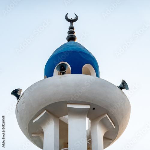 Fotografia, Obraz  White and blue painted tip of a minaret with loudspeakers and a bronze crescent