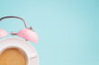 Leinwanddruck Bild - Pink alarm clock and coffee cup on blue background. Breakfast time concept. Minimal style
